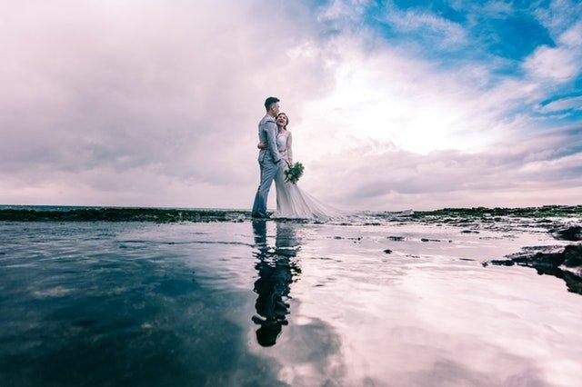 Ženích a nevesta so svadobnou kyticou stoja uprostred jazera.jpg