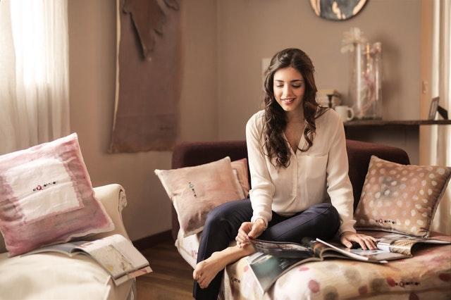 Žena sedí na posteli a číta časopisy