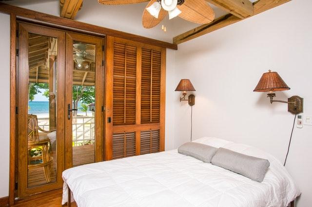 Izba s drevenými posuvnými dverami a veľkou bielou posteľou